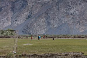 Young men playing football in front of the mountains
