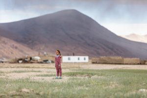 Little girl standing in front of some houses
